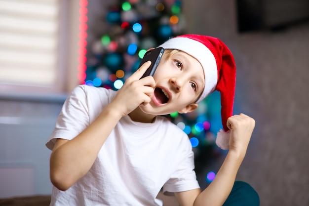 クリスマスのサンタの帽子をかぶった子供がバックグラウンドで花輪と電話で話している