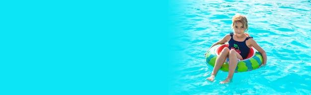 輪になっている子供がプールで泳ぎます。セレクティブフォーカス。子供。