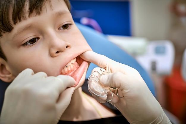 医者の予約で歯科医の椅子に座っている子供。