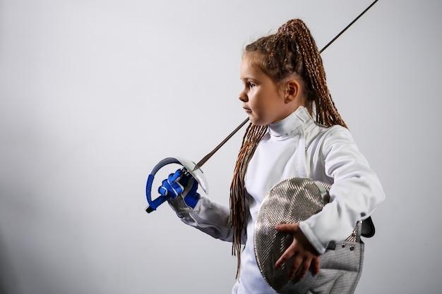 펜싱 복장을 한 아이가 에페를 들고 있습니다. 펜싱을 배우는 소녀