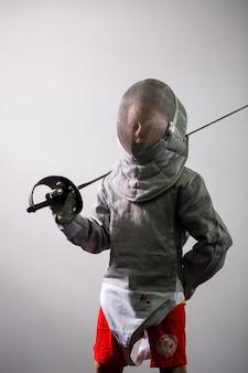 Ребенок в костюме фехтовальщика держит шпагу. девушка учится фехтованию