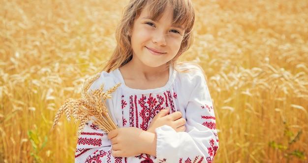Ребенок в поле пшеницы в вышитой рубашке. украинец.