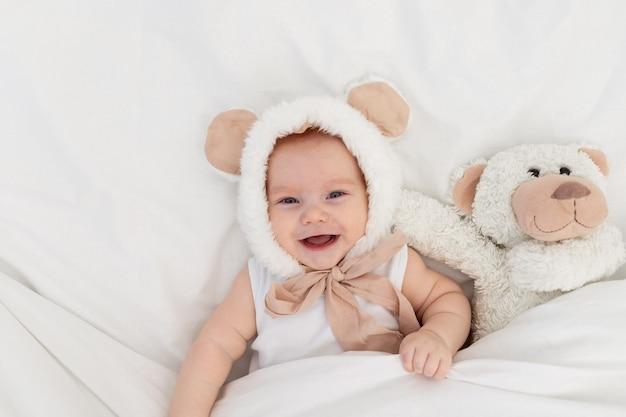 담요 아래 테 디 베어와 함께 귀를 가진 재미있는 모자에있는 아이. 어린 이용 섬유 및 침대 린넨. 신생아가 깨어 났거나 잠자리에들 것입니다.