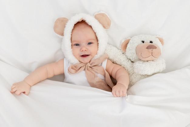 담요 아래에 테디베어가 있는 귀가 있는 재미있는 모자를 쓴 아이. 어린이용 섬유 및 침대 린넨. 갓 태어난 아기가 일어났거나 자려고 합니다.