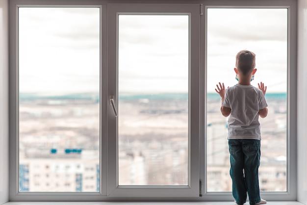 医療マスクをかぶった子供が、コロナウイルスとcovid -19のために隔離されて家に座っており、窓の外を見ています。