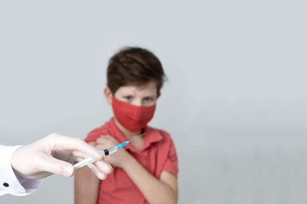 医療用マスクを着用した子供が、パンデミックでコロナウイルスの予防接種を受けています