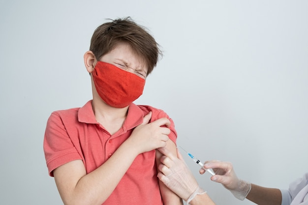 의료용 마스크를 쓴 어린이가 전염병에 걸린 코로나 바이러스에 대한 예방 접종을받습니다