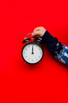 새해 스웨터를 입은 아이가 빨간색 배경에 검은색 시계를 들고 있다