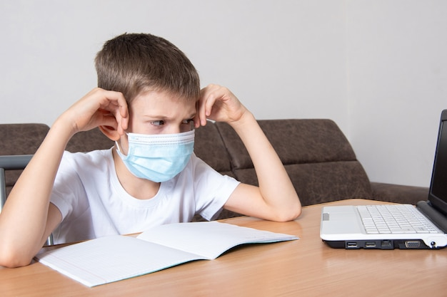 顔に保護マスクをかぶった子供はノートパソコンを不快に見ます。男の子は自宅でオンラインで遠隔学習します。子供は勉強したくありません。オンライン教育、ホームスクーリングのコンセプト