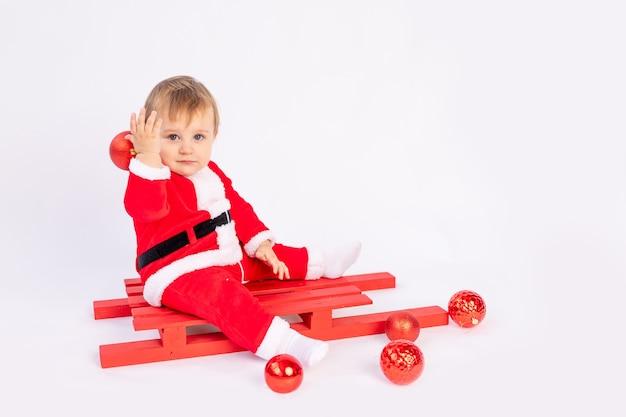 Ребенок в костюме санта-клауса с красными елочными шарами на белом изолированном фоне, концепция нового года и рождества, место для текста