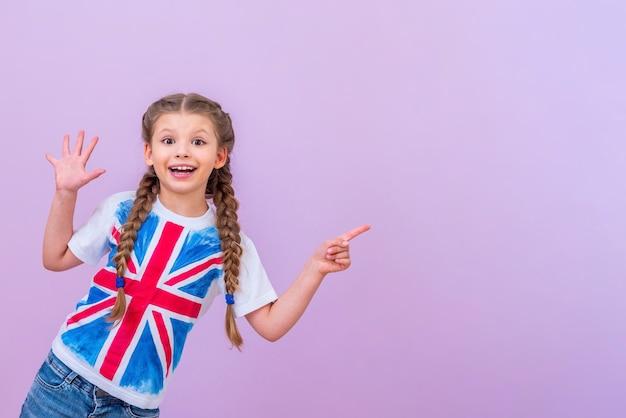 영국 국기가 달린 셔츠를 입은 아이가 격리된 분홍색 배경에 있는 귀하의 광고를 가리킵니다.