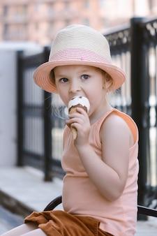 Ребенок в соломенной шляпе сидит на скамейке. маленькая девочка ест мороженое.