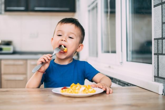 부엌에서 티셔츠를 입은 아이가 오믈렛을 먹고 스스로 포크
