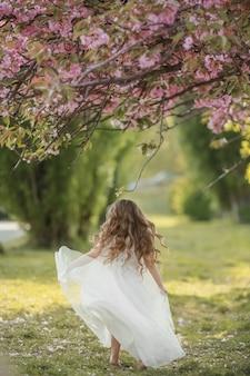 白いドレスを着ている公共の公園で緑の芝生に白い就学前のドレスを着た子供