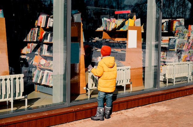 黄色いジャケットを着た子供が、通りの売店の窓を注意深く調べています。
