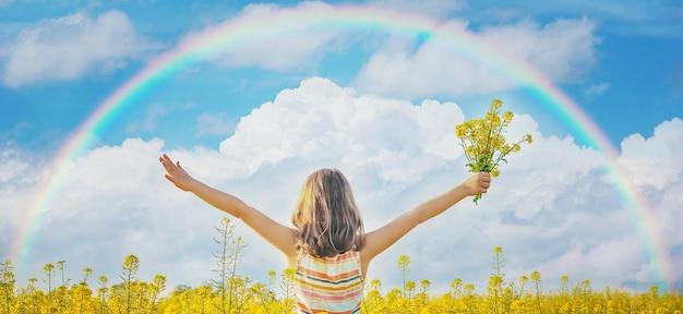 黄色い虹の野原にいる子供