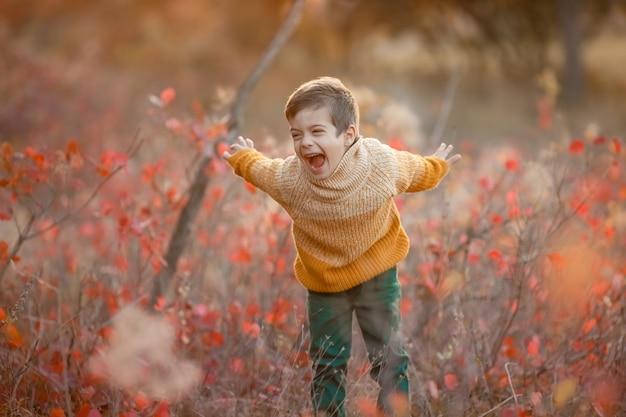 Ребенок в желтом свитере стоит на поляне с кричащей сухой травой и машет руками