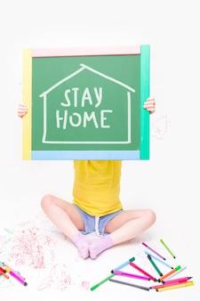 黄色のtシャツと青いショートパンツを着た子供が、家にいるという言葉が書かれた緑色の黒板を持っています