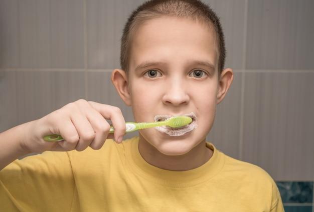 Ребенок в желтой футболке чистит зубы утром зубной щеткой. в ванной.