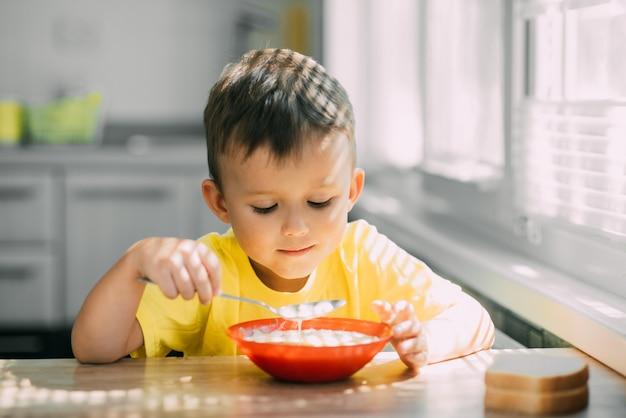 オクローシカと呼ばれる国のロシア料理を食べるキッチンで黄色いtシャツを着た子供