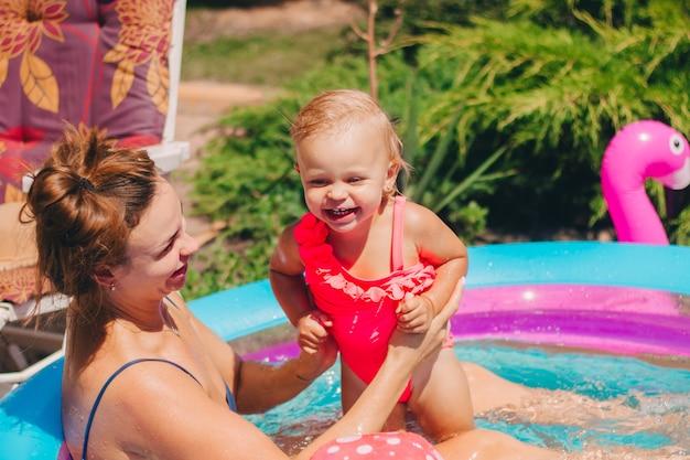 Ребенок в надувном бассейне купается во дворе с мамой