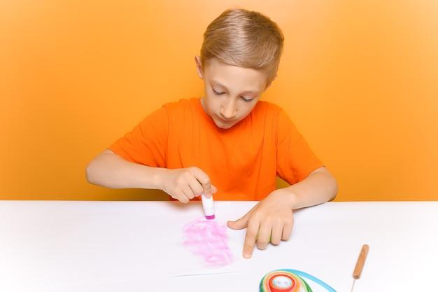 オレンジ色のtシャツを着た子供が白い紙に接着剤を塗り、クイリング技術で作られた薄いツイストストリップの接着を防ぎます。