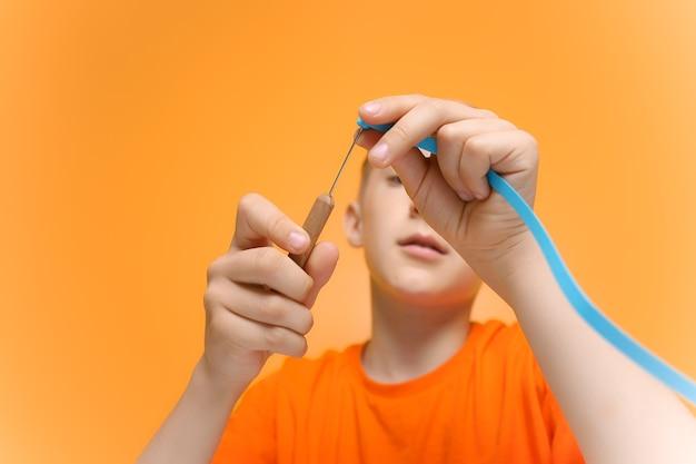 オレンジ色のtシャツを着た子供が、紙の薄いクイリング技法のストリップをねじるためのツールを手に持っています。