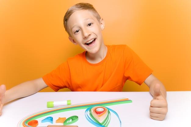 オレンジ色のtシャツを着た子供がカメラを笑ってから、クイリングのテクニックで薄い紙片をひねります。