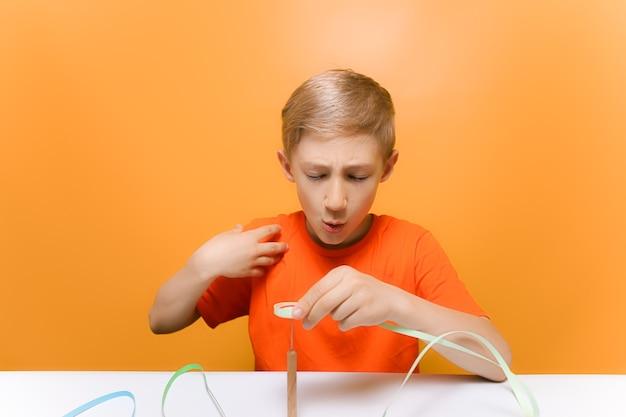 オレンジ色のtシャツを着た子供が、薄い紙片をねじるためのクイリングツールを指で刺しました。