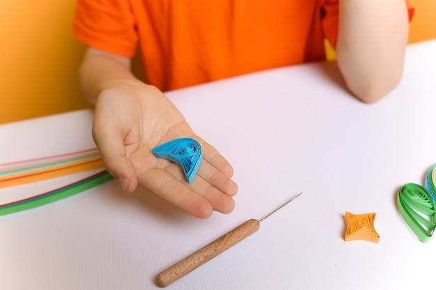 オレンジ色のtシャツを着た子供が、クイリング技法でねじれた紙片を見せています。少年はそれらを紙に接着するためにブランクを準備しました