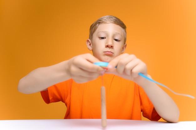 オレンジ色のtシャツを着た子供がテーブルに座って、紙の薄いストリップのねじれを見ています。自家製はがき用のブランクを作ります
