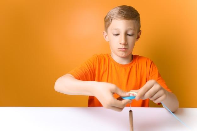 オレンジ色のtシャツを着た子供がテーブルに座って、クイリングツールで薄い紙片をひねります