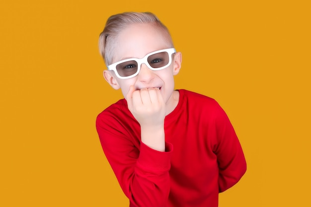 어린이용 3d 안경을 쓴 아이가 놀라 손톱을 물어뜯는다.