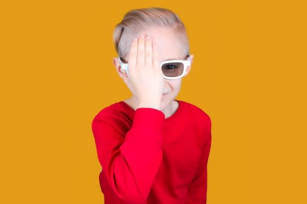 어린이용 3d 안경을 쓴 아이가 손으로 눈을 가렸습니다