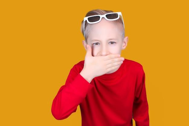 어린이용 3d 안경을 쓴 아이가 손으로 입을 가렸다