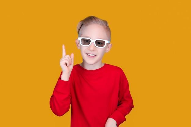 어린이용 3d 안경을 쓴 아이가 노란색 배경에 손가락을 올렸다