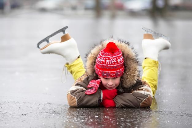 冬のフィギュアスケートの子供が氷の上に横たわって微笑む。