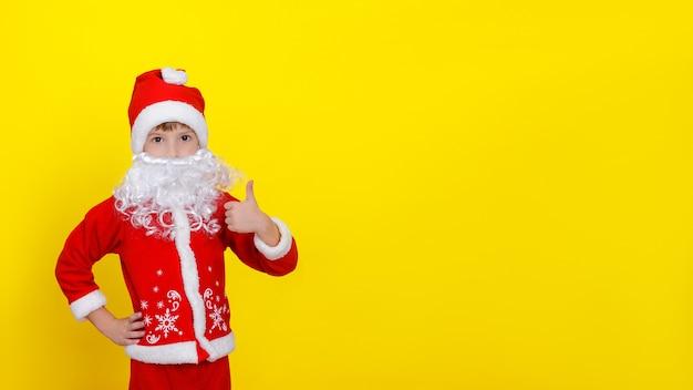 산타클로스 옷을 입은 아이와 인조 수염이 손으로 엄지손가락을 치켜든다