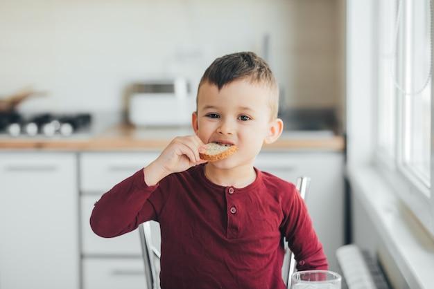 バーガンディのセーターの白い光のキッチンで午後の子供がオムレツを食べる
