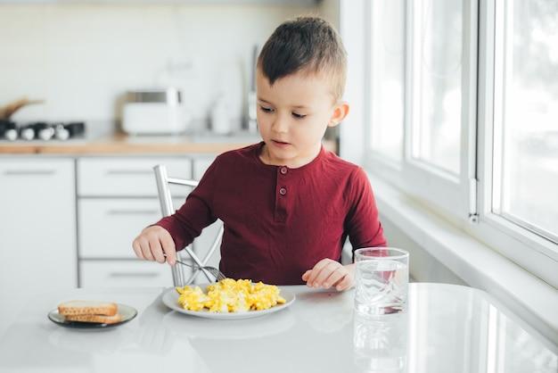 Ребенок днем на белой светлой кухне в бордовом свитере ест омлет