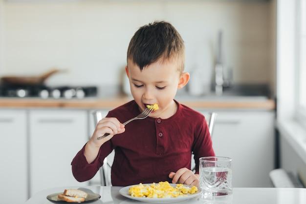 부르고뉴 스웨터를 입은 흰 빛 부엌에서 오후에 아이가 오믈렛을 먹는다.
