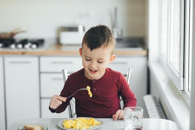 오후에 버건디 스웨터를 입은 흰색 조명 주방의 한 아이가 오믈렛을 먹습니다