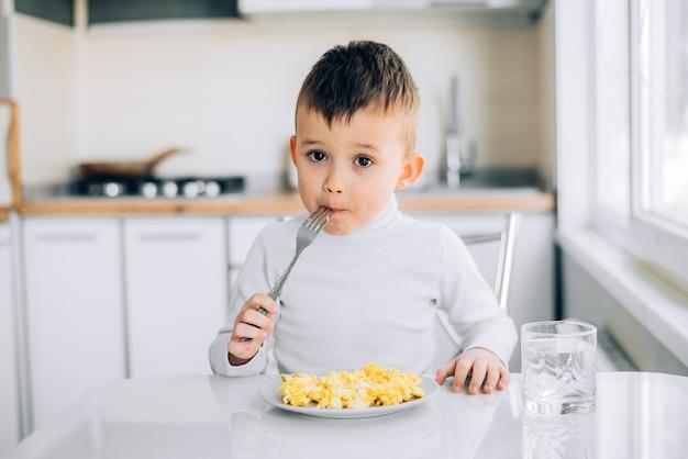 하얀 스웨터를 입은 하얀 빛 부엌에서 오후에 아이가 오믈렛을 먹는다.