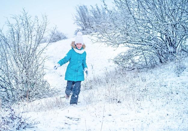 겨울 옷을 입은 아이가 달리고 있습니다. 눈 속에서 소녀입니다. 겨울 재미.