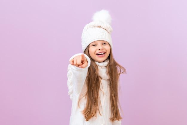 겨울옷을 입은 아이가 앞의 공간을 가리키며 고립된 분홍색 배경에 미소를 짓고 있습니다.