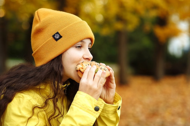 노란 옷을 입은 아이가 가을에 텍스트를 위해 공원 공간에 햄버거를 가지고 있다