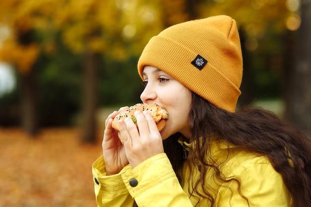 노란 옷을 입은 아이가 공원에서 가을에 햄버거를 가지고 있다