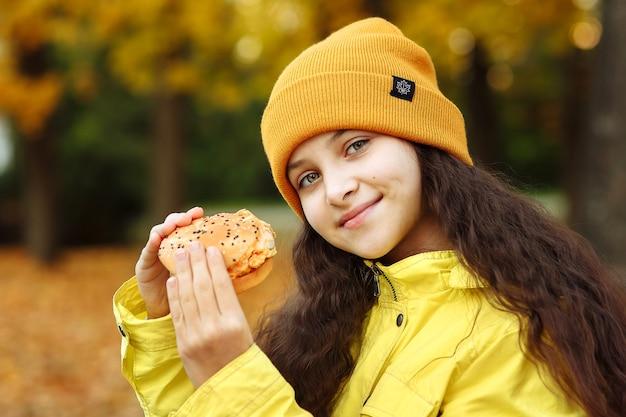 노란색 옷을 입은 아이가 햄버거를 손에 들고 공원에서 카메라를 보고 미소를 짓는다