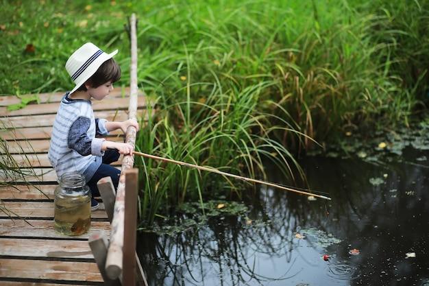 가을 아침에 한 아이가 낚시를 하고 있습니다. 연못에가 석양입니다. 산책로에 낚싯대를 든 어부.