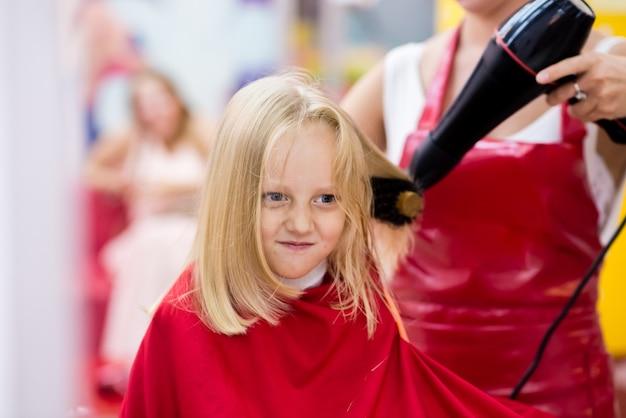 Ребенку делают стрижку в салоне красоты.
